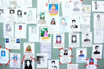 Board with photos of missing Rana Plaza garment workers, posted by relatives. Photo: Sharat Chowdhury. Licensed via Wikimedia Commons.