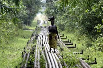 A woman walks along an oil pipeline near Shell's Utorogu Flow Station in Nigeria.