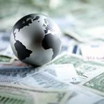 Metal globe resting on dollar bills