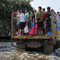 People standing on the back of a truck going through water