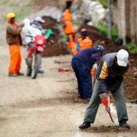 construction workers digging up road with pick ax
