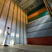 worker looking up at imposing stack of cargo containers